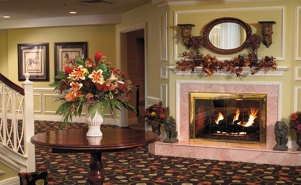 The Bristal Assisted Living at Westbury common area with cozy surroundings and roaring fire