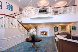 Lobby of The Bristal Assisted Living at Westbury with reception area and two level staircase leading up to second floor