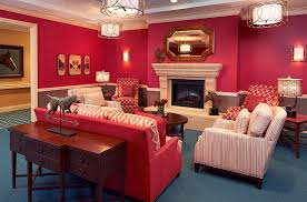 Community living room at The Bristal Assisted Living at Woodcliff Lake with rich red walls and a large fireplace