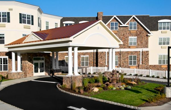 Exterior view of the front of The Bristal Assisted Living at Woodcliff Lake with covered driveway and entrance and manicured lawn