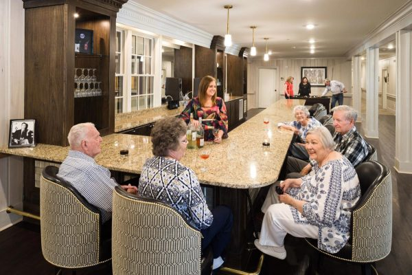 Alexander Guest House Senior Living residents seated at the bar in the lounge