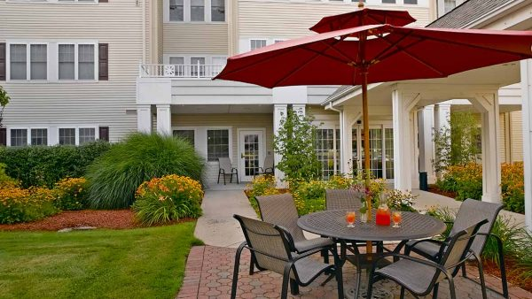 Red umbrella tables in the Atria Greenridge Place outdoor courtyard