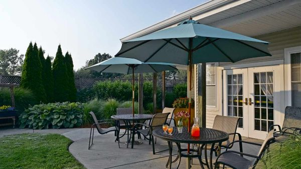 Atria Greenridge Place patio with umbrella tables at dusk