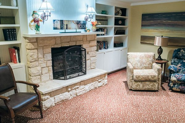 Community living room with fireplace in Brookdale Oak Hollow