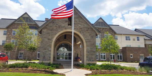 Brick faced covered entrance and American flag at Cahaba Ridge Retirement Community