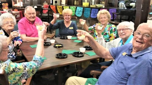 Seven seniors sitting at a table smiling and cheering with a drink in hand