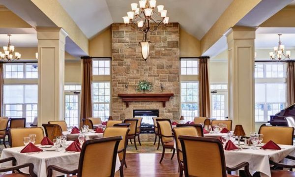 Waltonwood Providence dining room with a large stone fireplace