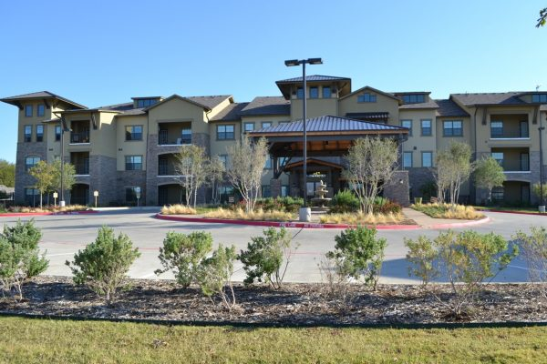 Building front and covered driveway leading up to Discovery Village At Twin Creeks