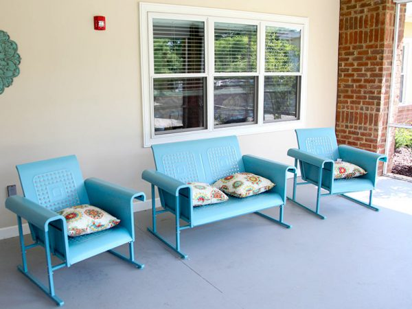 Blue chairs on a porch at Regency Retirement Village - Huntsville