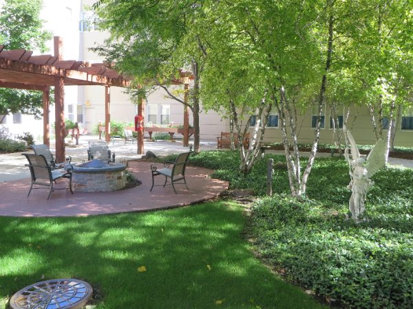 Outdiir courtyard witha firepit and trellis on the grounds of Milwaukee Catholic Home