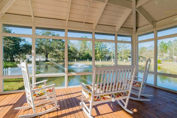 Covered porch with rocking chairs at LiveOak Village