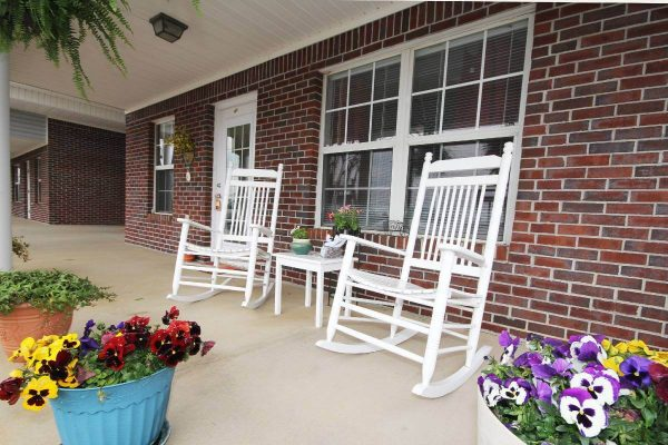 White rocking chairs surrounded by flowers on the porch of The Madison Village