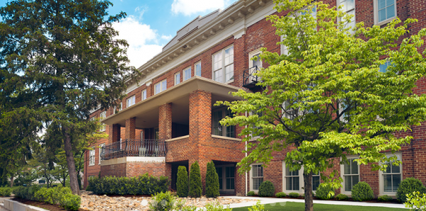 Exterior of the brick fascade at Oak Wood Place Senior Living with large covered balcony and green trees
