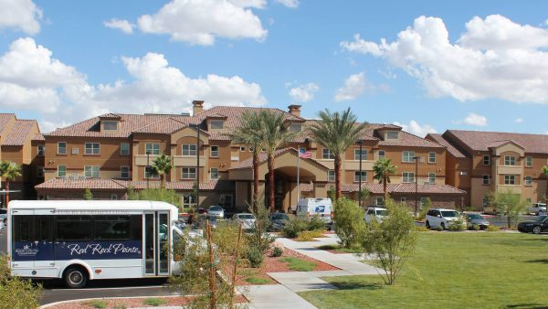Red Rock Pointe Retirement exterior view with grand palms, community bus and walkways leading up to covered entrance