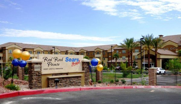 Entrance to Red Rock Pointe Retirement with signage or rock faced walls and balloons attached