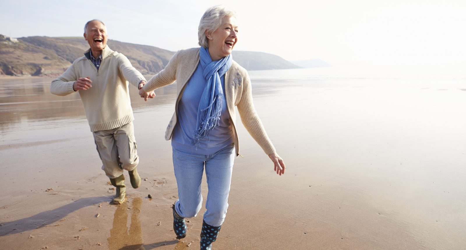 Senior man and woman holding hands and jogging on the beach