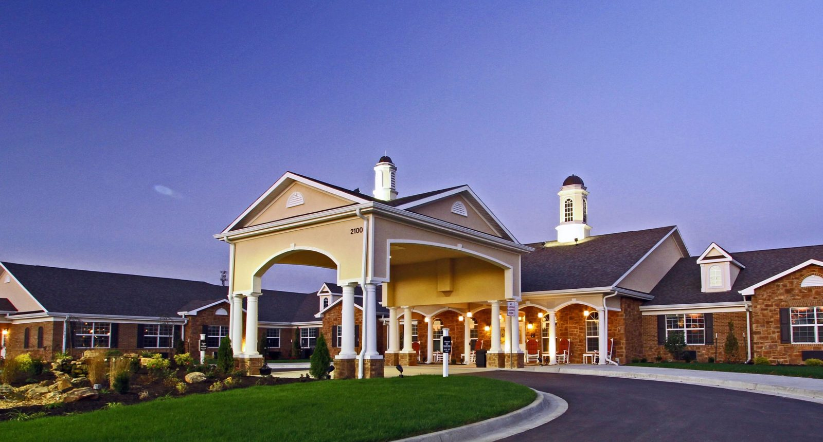 Upscale senior community with green lawn and covered entrance at dusk