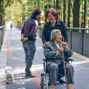 Senior woman in wheelchair being helped by woman on walking trail