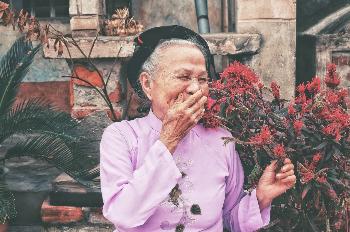 Senior Asian woman smiling and covering her mouth in front of red flowers