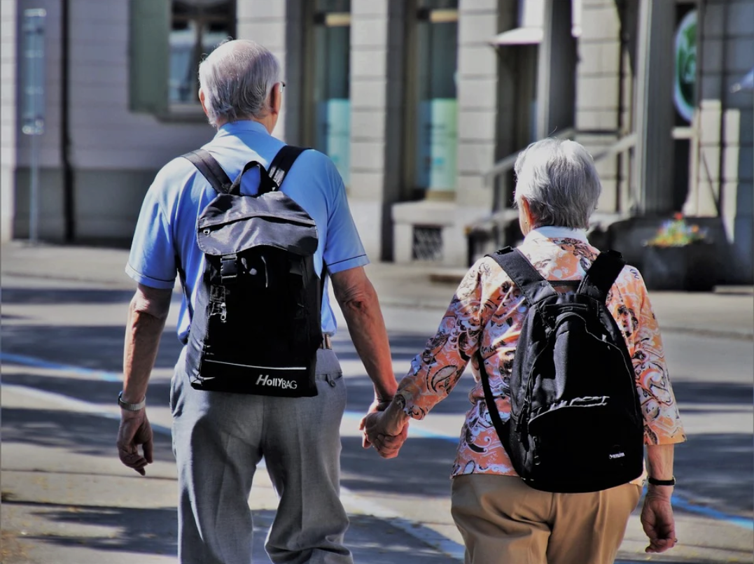Senior man and woman wearing backpacks and holding hands walking away