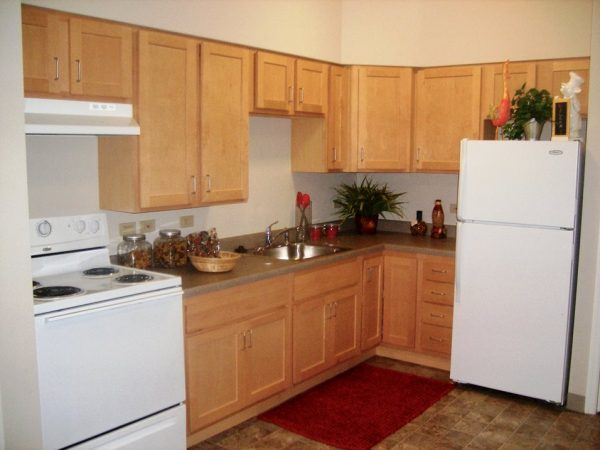 Grand South Senior Apartments model kitchen with light oak cabinets and white appliances