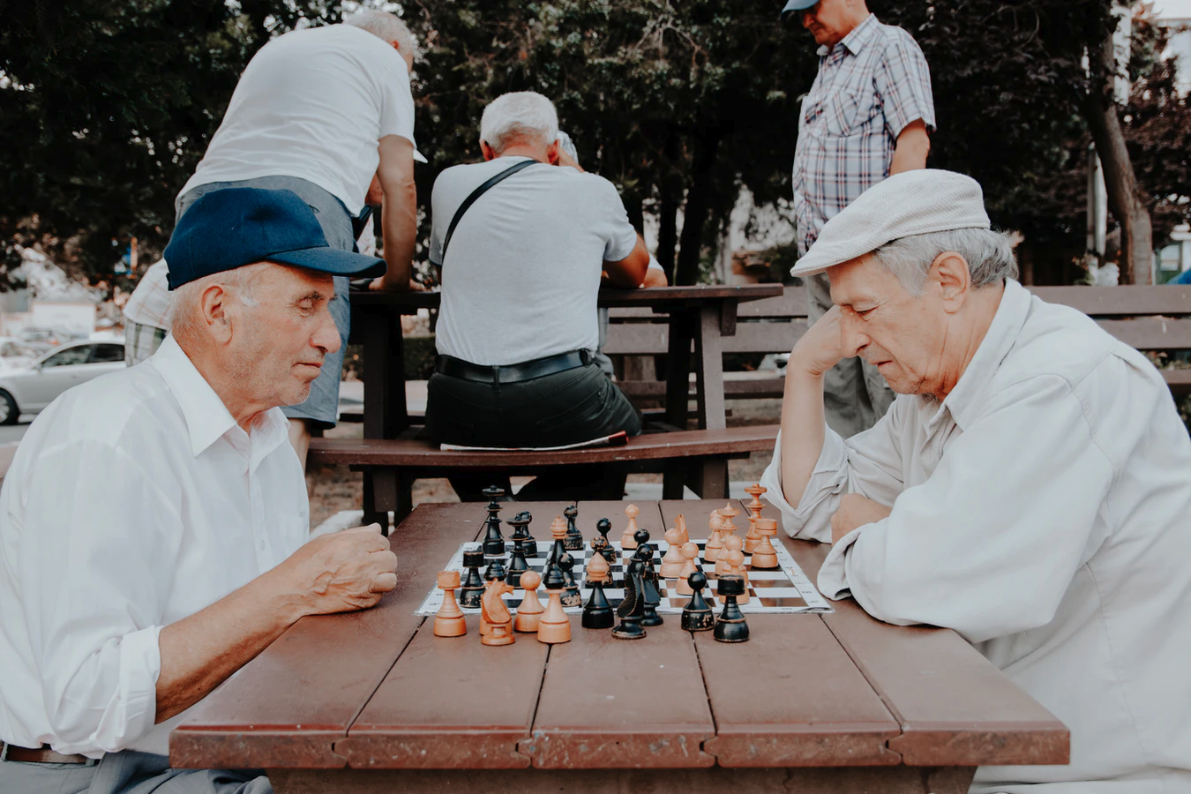 Two senior men in hats playing chess on a park picnic table