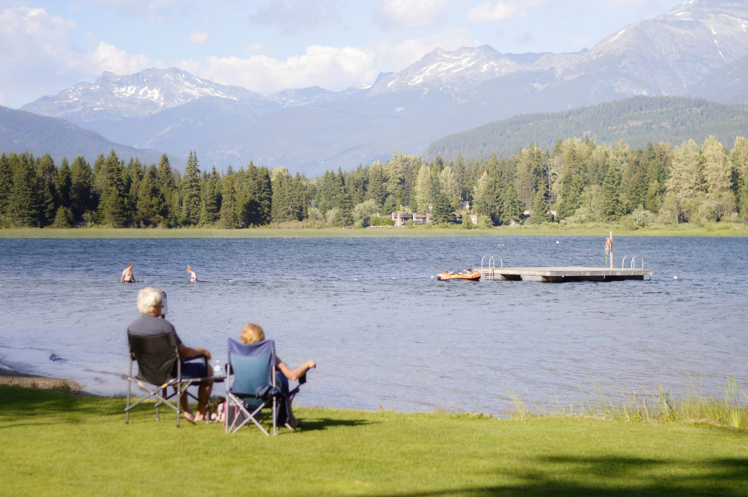 Senior couple sitting in chairs facing a lake with mountains in the background