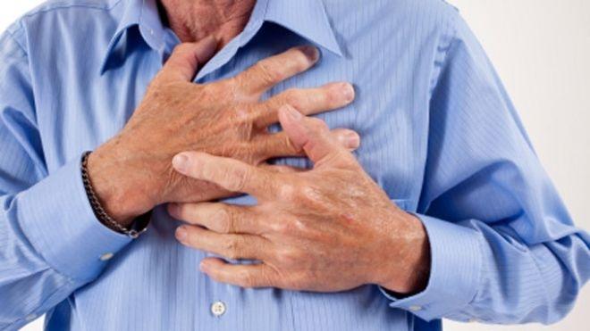 Senior mans hands clutching chest