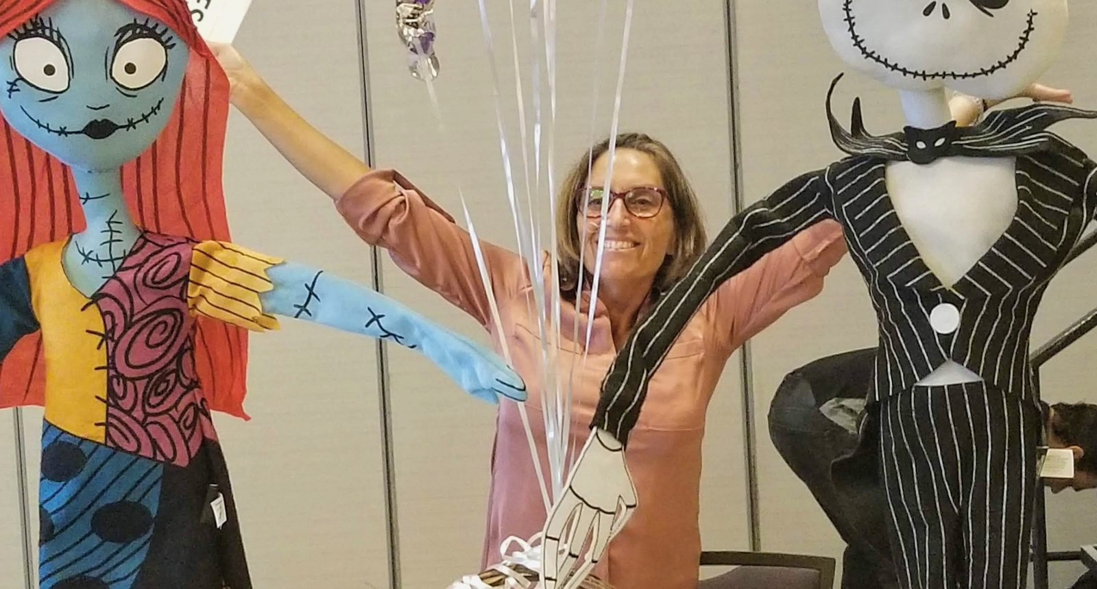 Female social worker with balloons and arms raised