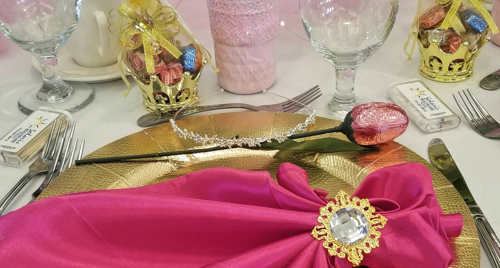 Table setting with pink napkin over gold plate