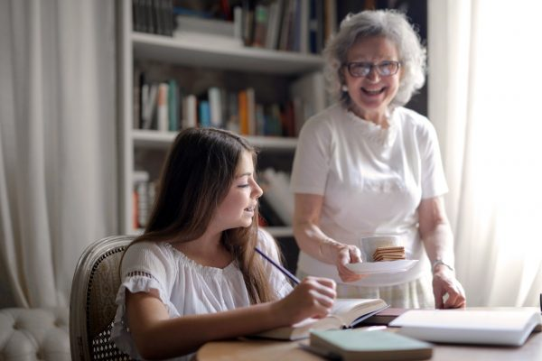 Senior woman bringing a snack to a young girl doing homework