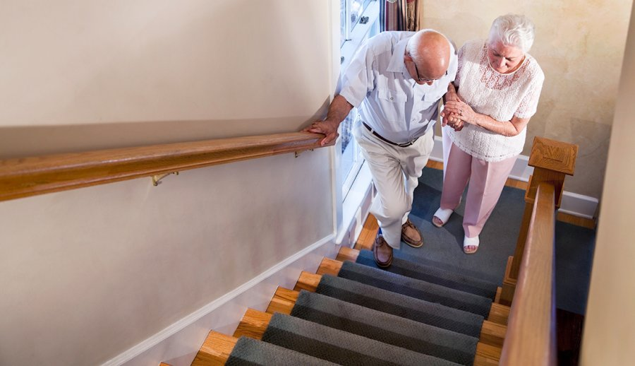 Senior man starting to walk up starirs with assistance from elderly woman