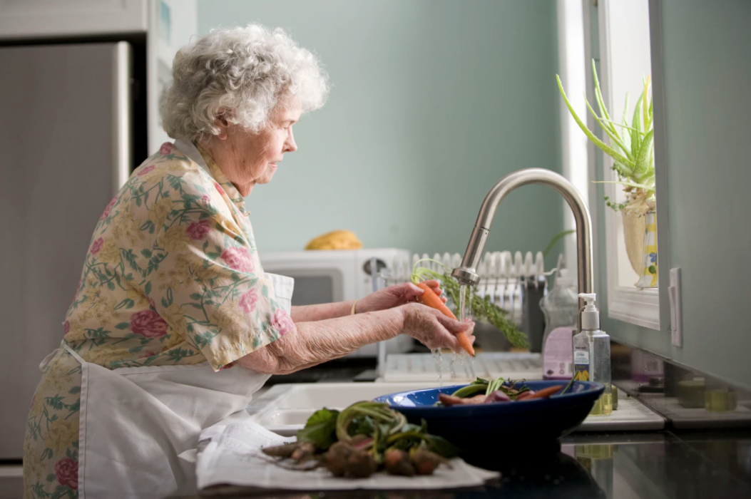 Senior woman in an apron washing a carrot off in the kitchen sink
