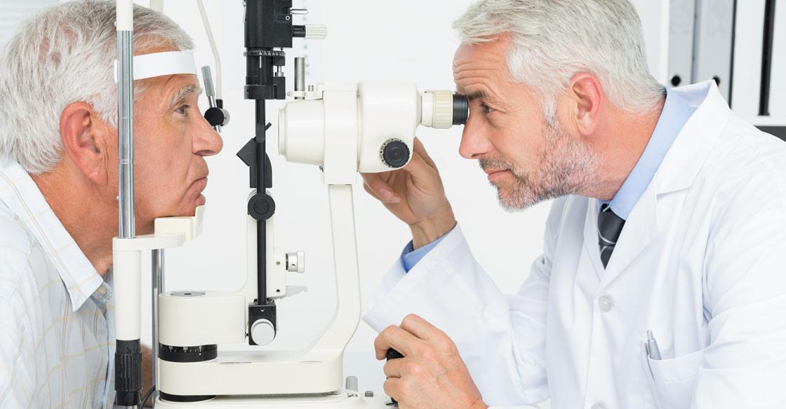 Senior man having his eyes checked by male optometrist