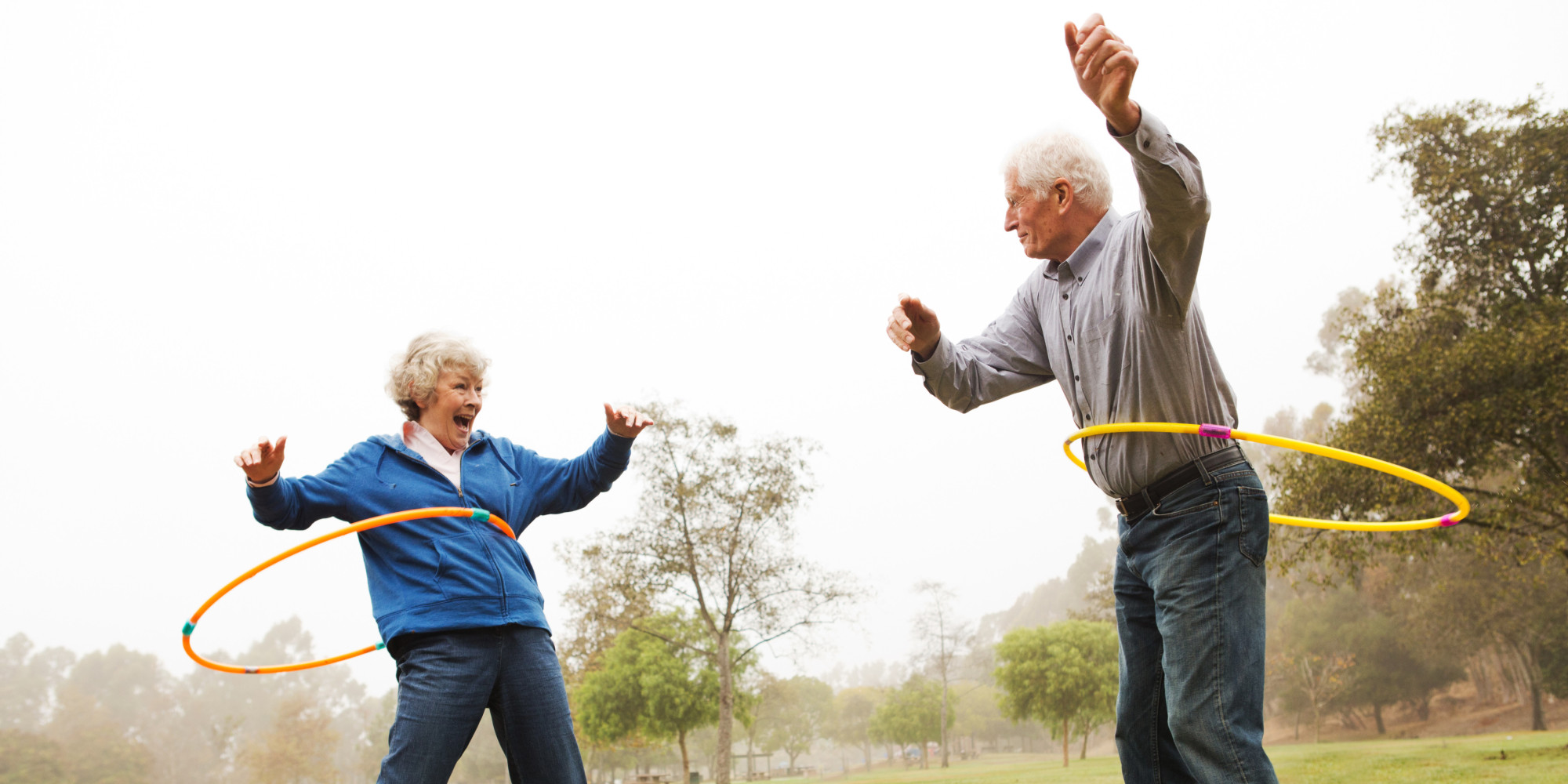 Senior couple using hula hoops in a park