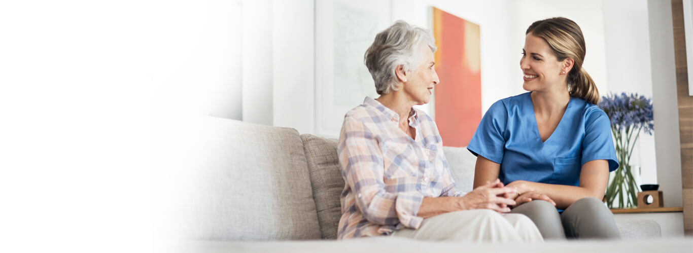 senior woman sitting on couch talking with a female caregiver
