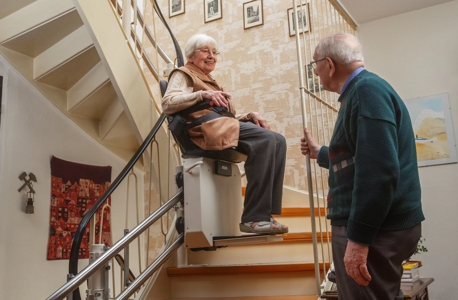 Senior man watching elderly woman use stair lift chair on curved staircase