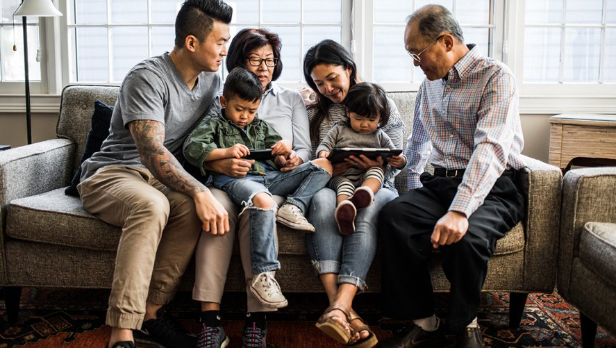 Multigenerational family members on a couch looking at tablets