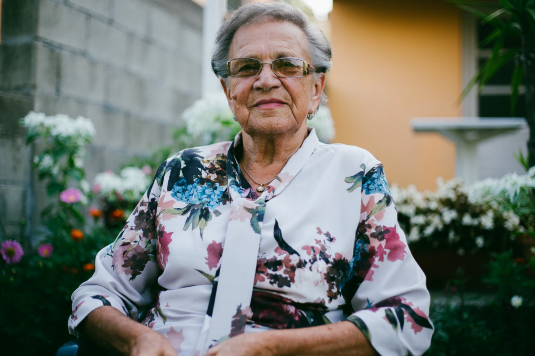 Senior woman in flowered shirt and glasses sitting in front of flowers and smiling