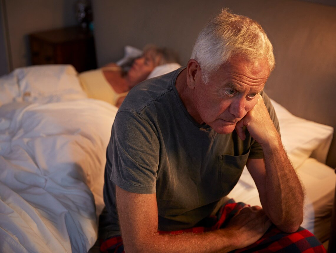Senior man sitting on edge of bed looking frustrated while senior woman sleeps behind him