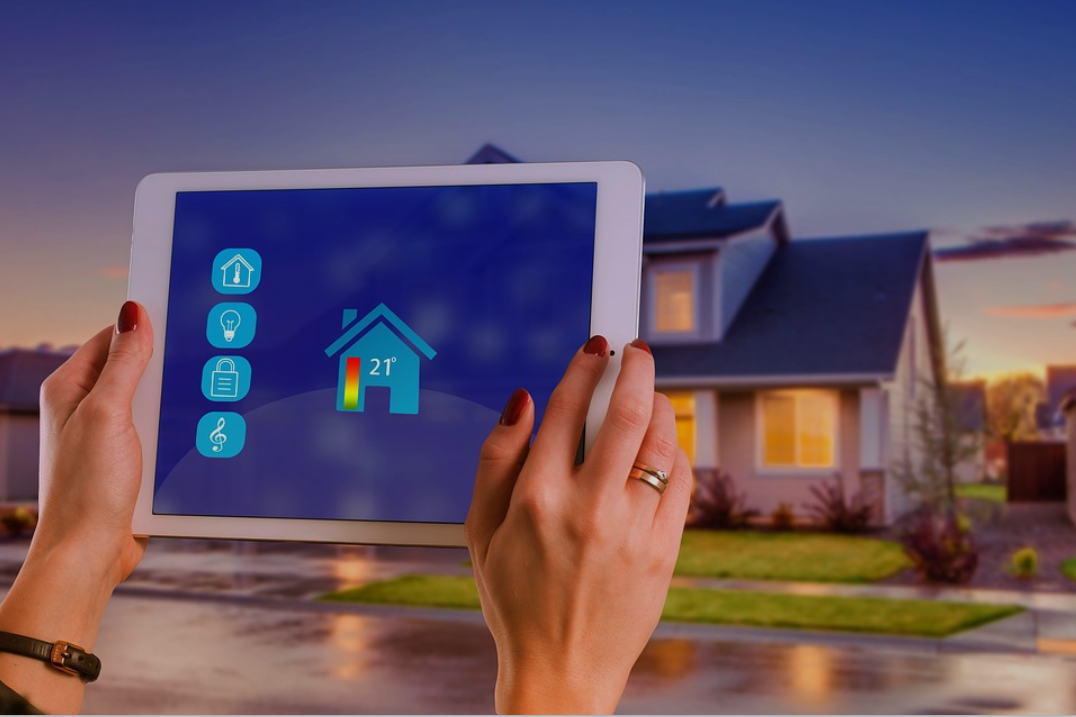 Womans hand touching a tablet in front of a home at dusk