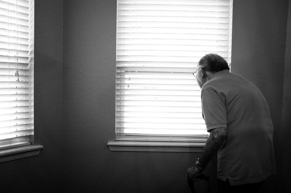 Senior man with cane looking out window through blinds