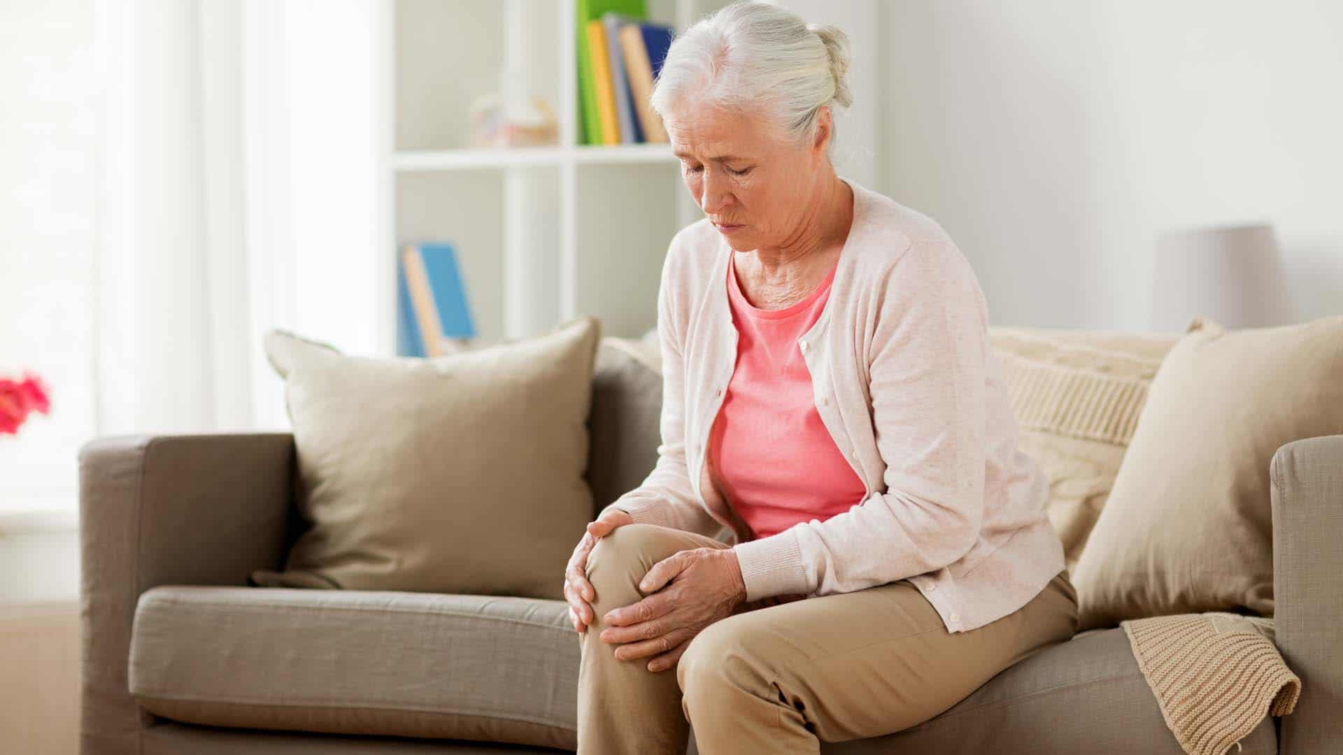 Senior woman sitting on couch grabbing knee and in pain