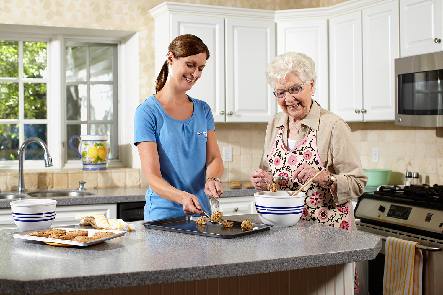 Senior woman cooking with a younger woman