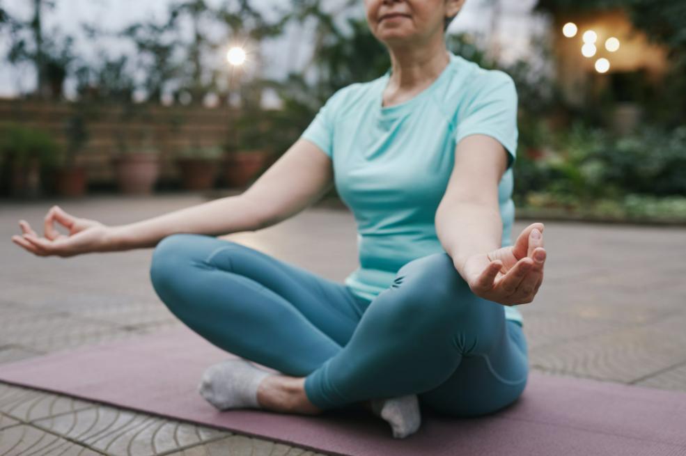 Senior woman in green sitting in a yoga pose