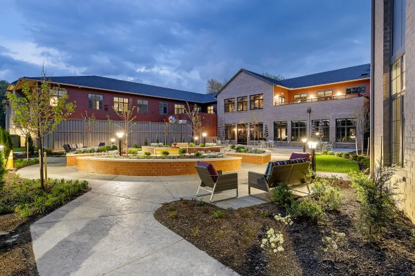Anthology Tan and brick exterior. Evening sky, circular garden and outdoor chairs on sidewalk.