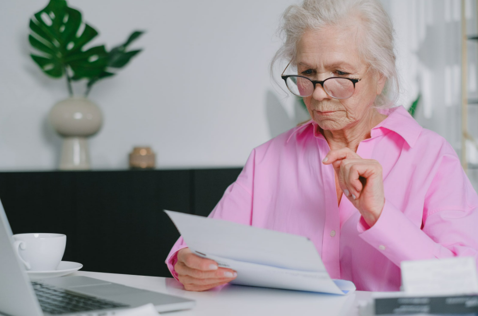 Senior woman in glasses and a pink shirt reviewing documents