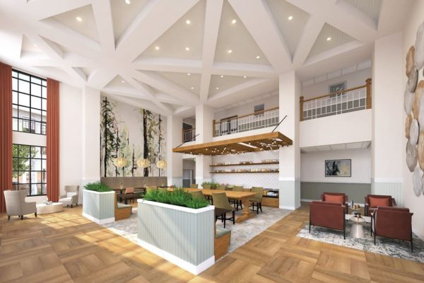 Anthology of Tuckahoe lobby with tall white ceilings, wood floors, white planters with green plants. Tall windows with red curtains and red chairs