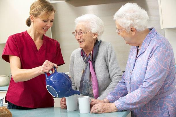 Female caregiver poring tea with two seniors