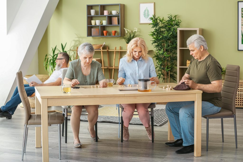Senior housing residents at a table drinking tea and playing games and utilizing tech innovations